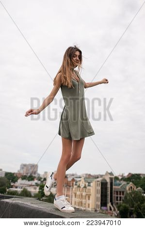 Pretty girl walking on the roof in the big city. Internal and external balance. Inner harmony.