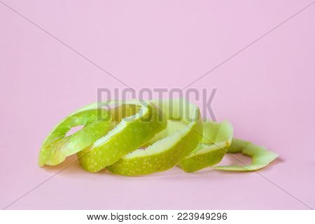 green apple peel on pink background as a symbol of recycling circulate economy