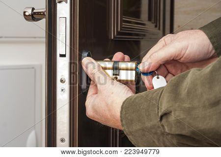 Locksmith replacing a cylinder lock of an entrance door.