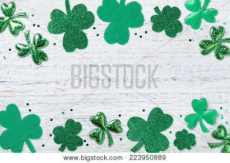 Saint Patricks Day border with green shamrock on white rustic board top view.