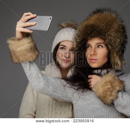 Two girls in winter clothes doing selfie on smarphone. Isolated on grey background.