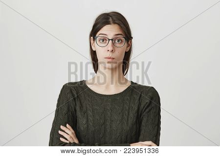 Portrait of smart attractive young woman with crossed hands in dark-green sweater and glasses with confident and smug expression over white background. No I don't want to share my lecture notes.