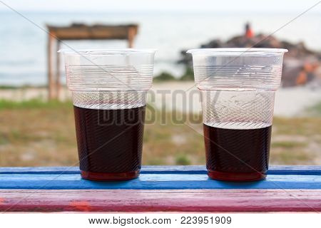 Two plastic glassof wine stands on the colored bench, the sea and the catamarans in the background