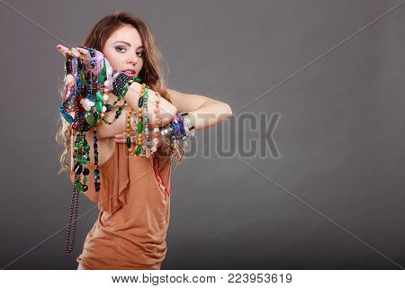 Pretty young woman wearing bracelets and rings holding many plentiful of precious jewelry necklaces beads. Portrait of gorgeous fashion girl in studio on gray.