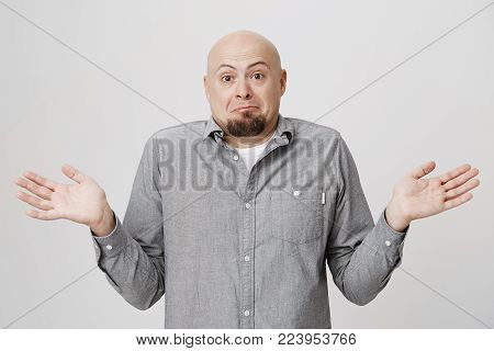Studio shot of emotional clueless bald man dressed in gray shirt over white t-shirt having confused puzzled look, frowning face, shrugging shoulders as he doesn't know reason of accident