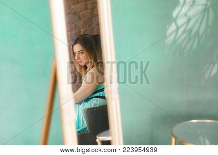 A closeup mirror reflection of a woman, selective focus. Green loft wall on background with copyspace