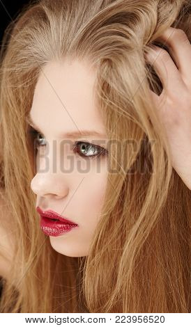 Portrait of woman with long blond hait and red lips.