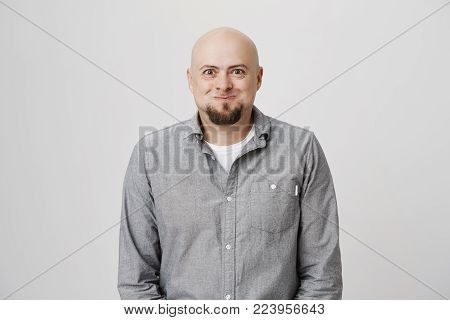 Fashionable bearded bald guy keeps lips rounded, wears gray shirt, isolated against gray concrete background. Unshaven hairless male pouts lips and has surprised expression