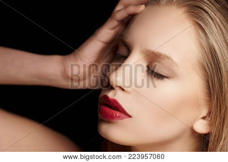 Close up portrait of  blond female with red lips isolated on black background.
