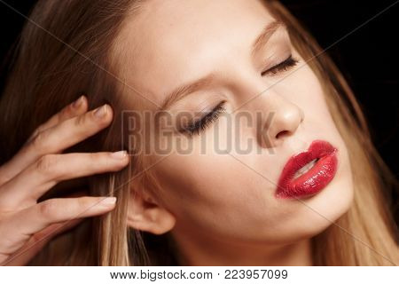 Close up portrait of blond young woman with make up and red lips.
