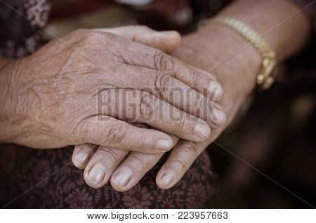 Hands Asian elderly woman grasps her hand on lap, pair of elderly wrinkled hands and Traces of hard work, World Kindness older and Adult care  concept. Senior citizen is a common euphemism for an old person