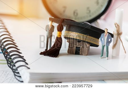 Miniature figurine Businessman standing near graduation cap on notebook with notes paper background. Graduate study international abroad concept. Graduate study abroad program for students foreign