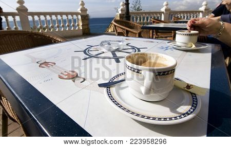 Coffe On The Table In The Bright Early Morning Sun In Benidorm, Spain.
