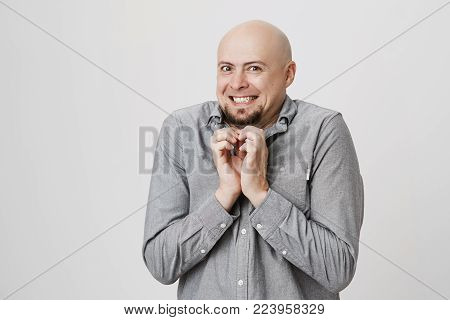Horizontal portrait of bald bearded man in gray shirt poses against gray background, mysteriously looks at camera, builds vicious plans, clenches teeth. Hairless male model expresses negative emotions.