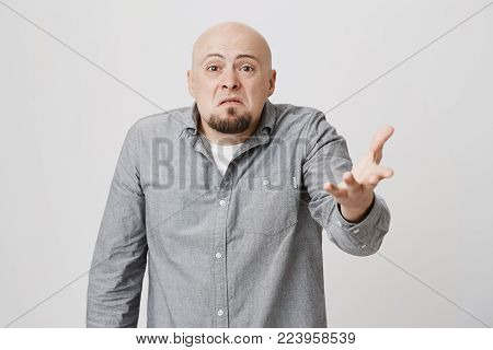 So what, Who cares. Aggressive bald european bearded man wearing gray shirt shrugging his shoulders in questioning gesture of uncertainty and having irritated clueless look