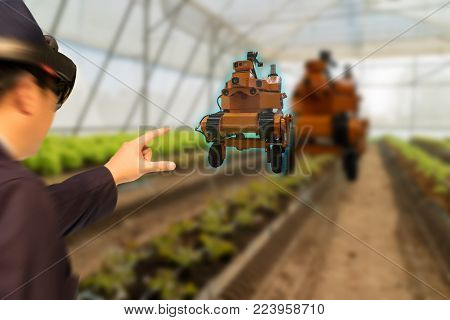 iot smart industry robot 4.0 agriculture concept,agronomist,farmer(blurred) using smart glasses (augmented mixed virtual reality,artificial intelligence technology) to monitoring  autonomous robotics