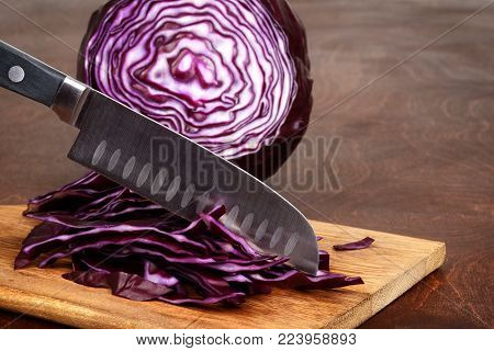 closeup slicing red cabbage with knife on a cutting board