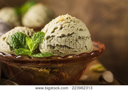 Pistachio ice cream scoops with grated pistachos in red glass bowl on old wooden table background. Homemade summer food concept with copy space.
