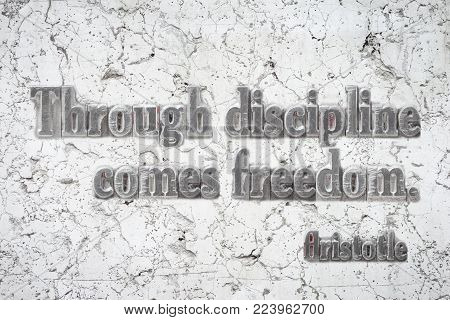 Through discipline comes freedom - ancient Greek philosopher Aristotle quote mounted on white marble wall