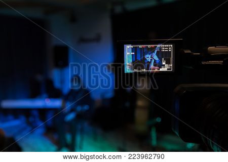 The LCD display on the camcorder. Filming the concert. Musicians playing the double bass, synthesizer and guitar