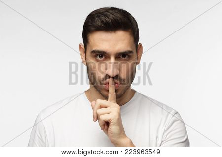Close up shot of handsome strict man with shh gesture, asking for silence or to be quiet, isolated on gray background