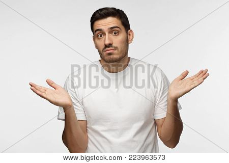 I don't know. Young man isolated on grey background being at a loss, showing helpless gesture with arm and hands, mouth curved as if he does not know what to do