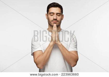 Closeup of young man in white tshirt isolated on gray background looking stressed, putting hands together as if he is praying with closed eyes to overcome depression