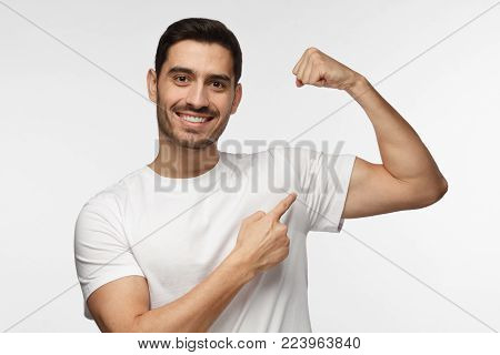 Young Strong Sporty Athletic Man In White T-shirt, Shows Biceps After Training In Gym, Isolated On G