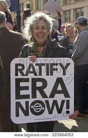 Asheville, North Carolina, USA - January 20, 2018: Still fighting for an Equal Rights Amendment for women for over 50 years, an older woman standing in a crowd of demonstrators holds a sign saying