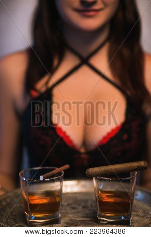 Sexy woman holding a tray of alcohol drinks and cigarettes. Bad habits. Immoral lifestyle. Elite night clubs for rich people concept