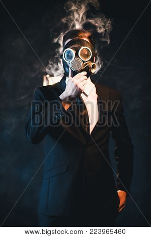 Man covered in smoke and wearing a gas mask. Dangerous influence of smoking addiction. Health hazard concept