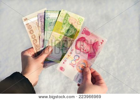 A man's holding a bundle of Chinese money on the snow background. Banknotes of one hundreds, twenty and ten RMB