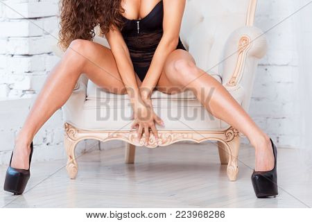 Perfect, sexy legs and ass of young woman wearing seductive black lingerie sitting on luxury vintage chair.