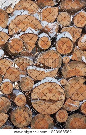 Pile of timber wood laying covered with snow background