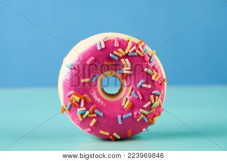 Pink frosted doughnut with colorful sprinkles, on blue background.