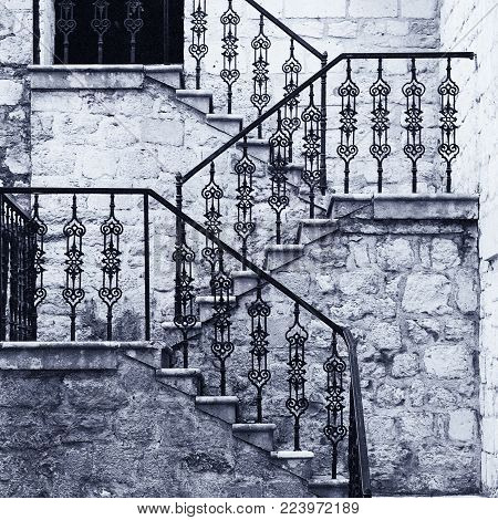 Ancient stone staircase with ornate wrought handrail, old monochrome film effect