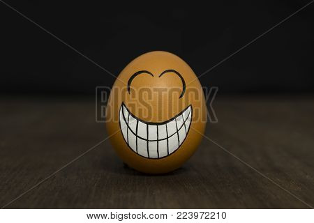 Egg with a joyful smiley. The mouth is wide open. He smiles.