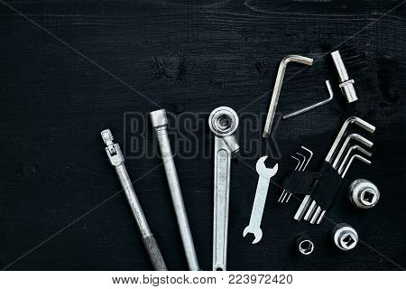 Tools for car repair in Workshop. Car repair equipment on black wooden background in car repair shop. Top view. Copy space. Still life. Flat lay