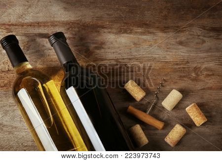 Two bottles with red and white wine on wooden background