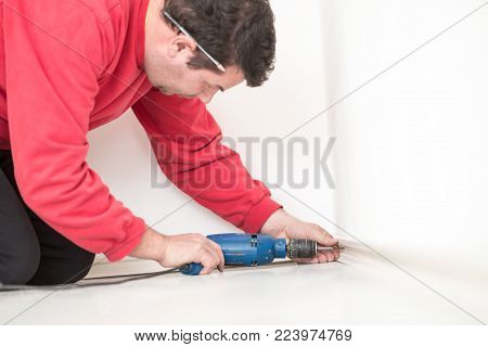 Man worker in red shirt kneeling on the floor drilling a hole in a white interior wall with a small handheld electric drill.