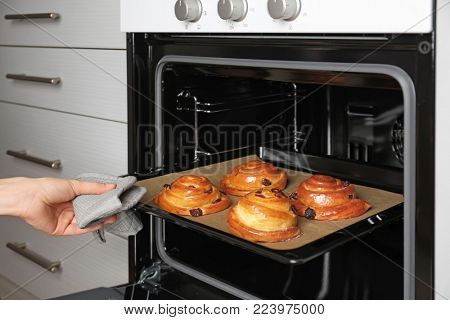 Woman taking baking sheet with buns from oven, closeup