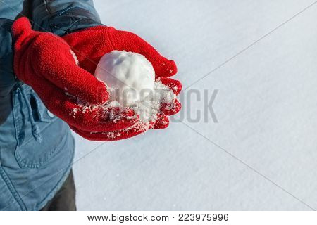 hands in red gloves holding snowball on the snow background. Winter season, vacation, games concept. Copy space
