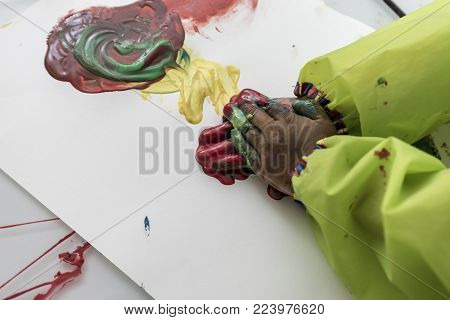 Child wearing protective clothing playing with colorful paints doing hand painting daubing pigment onto paper in an abstract design.