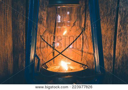 Old kerosene lamp illuminates the old wooden wall