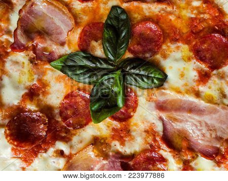 Pepperoni pizza background with pieces of salami bacon and melted cheese. Fattening and delicious meal with lots of meat
