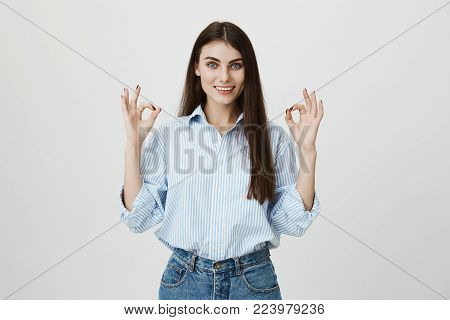 Attractive young european female student in blue shirt and jeans, showing okay or fine gesture while smiling broadly and standing over gray background. I definitely approve your idea to visit bar.