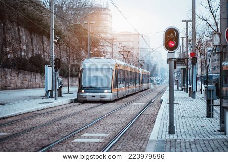 Outdoor metro or tram stop, two railway tracks, sidewalk of pavement stone, red traffic light and modern curved train with yellow stripes and huge glass windows on dull winter day, Porto, Portugal