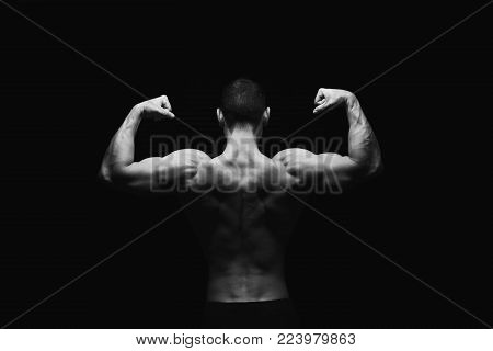 Unrecognizable man bodybuilder shows strong hands and back muscles, athletic trapezius. Low key, studio shot on black background, black and white image