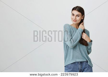 Waist-up portrait of Caucasian beautiful attractive young female model with long dark hair dressed in casual clothes posing indoors, pleased to hear compliments, touching her hair. Young woman expressing positive emotions