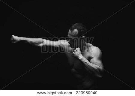 Athletic man make punch. Handsome fitness model show strong hands, shoulder muscles and biceps. Studio shot on black background, low key. Kickboxing and fight sport concept, black and white image